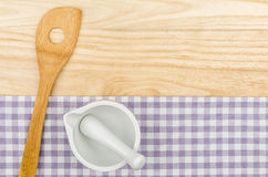 Wooden spoon and mortar on a purple checkered table cloth. On a wooden background Royalty Free Stock Photos