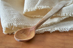 Wooden spoon and napkin on chopping board Royalty Free Stock Photography