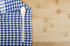 Wooden spoon and napkin on wooden table Royalty Free Stock Photography