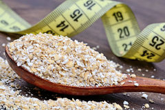 Wooden spoon with oat and centimeter Royalty Free Stock Images