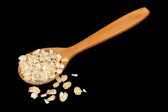 Wooden Spoon with Oat Flakes on Black Background Royalty Free Stock Photo
