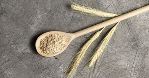 Wooden spoon with oats on table Royalty Free Stock Images