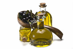 Wooden spoon, olives and oil. A big wooden spoon with olives and some bottles of olive oil isolated on a white background Stock Images