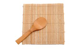 Wooden spoon over bamboo placemat Royalty Free Stock Image