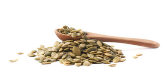 Wooden spoon over pumpkin seeds Royalty Free Stock Photos