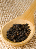 Wooden spoon with pepper over straw. Pepper in a wooden spoon over straw Stock Photo