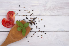 Wooden spoon with a piece of basil, tomato and pepper mixture. Stock Image