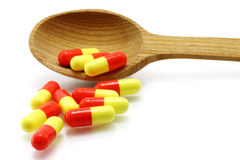 Wooden spoon with pills Royalty Free Stock Photos