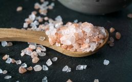 Wooden spoon with pink himalayan salt macro royalty free stock image