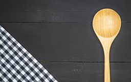 Wooden spoon. With plaid tartan tablecloth on black wooden table in top view Stock Images