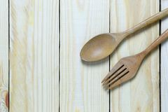 Wooden spoon rests on a brown wood floor. Wooden spoon rests on a brown wood floor and has copy space for your design ideas Stock Image