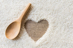 Wooden Spoon on rice background Space in the middle of a heart Stock Photo