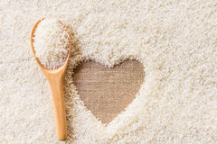 Wooden Spoon on rice background Space in the middle of a heart Royalty Free Stock Images