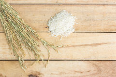 Wooden spoon with rice and paddy pile on wood Royalty Free Stock Photo