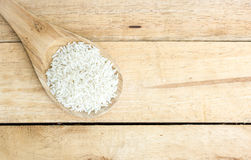 Wooden spoon with rice on wood Royalty Free Stock Photography