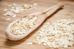 A wooden spoon with rolled oats. On a bamboo background Royalty Free Stock Image