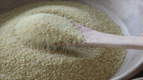 Scooping CousCous. Wooden spoon scooping dry couscous from wooden bowl