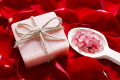 Wooden spoon with sea salt and bar of soap on rose petals backgr Stock Photos