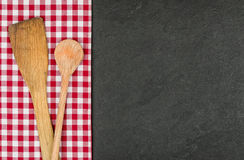 Wooden spoon on a slate plate with a checkered tablecloth. Wooden spoon on a slate plate with a red checkered tablecloth Royalty Free Stock Images