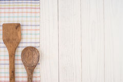 Wooden spoon and spatula on a napkin and an old white wooden tab Stock Images
