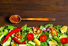 Wooden Spoon with Spices and Organic Food Background of Lettuce. Italian Cooking, organic food concept.Top view, copy space stock photo