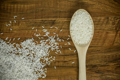 Wooden spoon and spilled rice Royalty Free Stock Photos