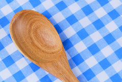 Wooden spoon,  tablecloth, fork on table. Background Royalty Free Stock Image