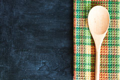 Wooden spoon and tablecloth. Over blackboard background Stock Photography