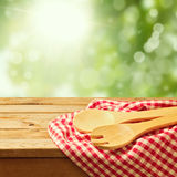 Wooden spoon on tablecloth over garden background Stock Photo