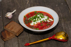 Wooden spoon, toast of black bread and a plate of borscht on the Stock Photography