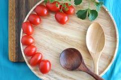 Wooden spoon on tray with fresh tomato Stock Photos