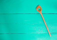 Wooden Spoon on turquoise wood as background Royalty Free Stock Photo