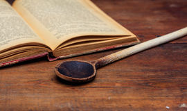 Wooden spoon and a vintage book Royalty Free Stock Photos