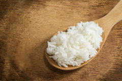 Wooden spoon white boiled rice on wood background Stock Photos