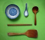 Wooden spoon, wood spoon, wood chopsticks, and blue ceramic bowls with blue ceramic spoons, flat lay on green background, yellow d. This photograph shows the Royalty Free Stock Image