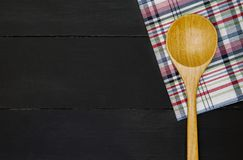 Wooden spoon. Over plaid tartan tablecloth on black wooden table in top view Royalty Free Stock Images