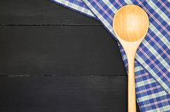 Wooden spoon. Over plaid tartan tablecloth on black wooden table in top view Stock Photos