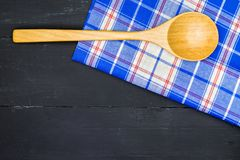 Wooden spoon. Over plaid tartan tablecloth on black wooden table in top view Royalty Free Stock Photography