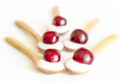 Wooden spoon is with yogurt and cherries Royalty Free Stock Image