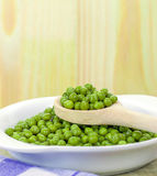 A wooden spoonful of fresh green peas Stock Images