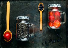 Wooden spoons and assorted berries and red fruits in glass jar on background of old rusty metals, concept of organic food stock photo