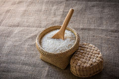 Wooden Spoons and basket of jasmine rice on wooden Stock Photos