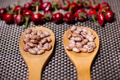 Wooden spoons with bean seeds and red pepper Royalty Free Stock Image