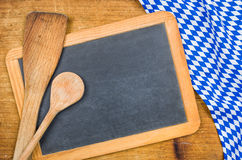 Wooden spoons and chalkboard with a bavarian tablecloth Stock Photos