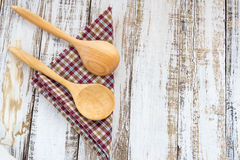 Wooden spoons on checkered cloth lying on wooden surface Royalty Free Stock Photo