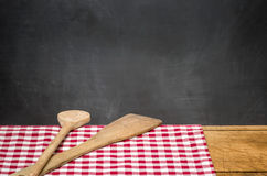 Wooden spoons on a checkered tablecloth in front of a blackboard. Two wooden spoons on a checkered tablecloth in front of a blackboard Stock Image