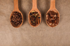 Wooden spoons with dessert spices. Wooden spoon with coffee beans, chocolate and spices for mulled wine lying on brown parchment Stock Photos