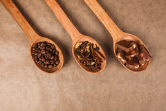 Wooden spoons with dessert spices. Wooden spoon with coffee beans, chocolate and spices for mulled wine lying on brown parchment Royalty Free Stock Photo