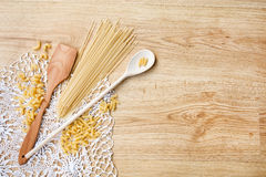 Wooden spoons, different pasta on knitted lace tablecloth Stock Images