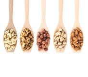 Wooden spoons full of different nuts Stock Image